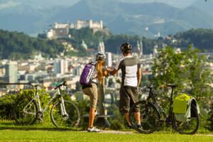 Pärchen beim Radfahren mit Blick auf Salzburg