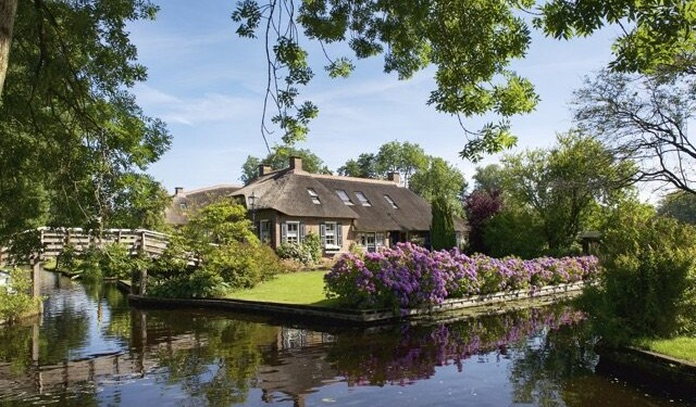 Giethoorn, The Netherlands - August 2, 2015: A cottage with a thatched roof in the village of Giethoorn in The Netherlands during a beautiful summer morning. View of a typical bridge and canal.