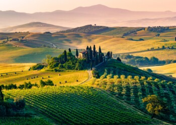 Val d'Orcia, Tuscany, Italy. A lonely farmhouse with cypress and olive trees, rolling hills.